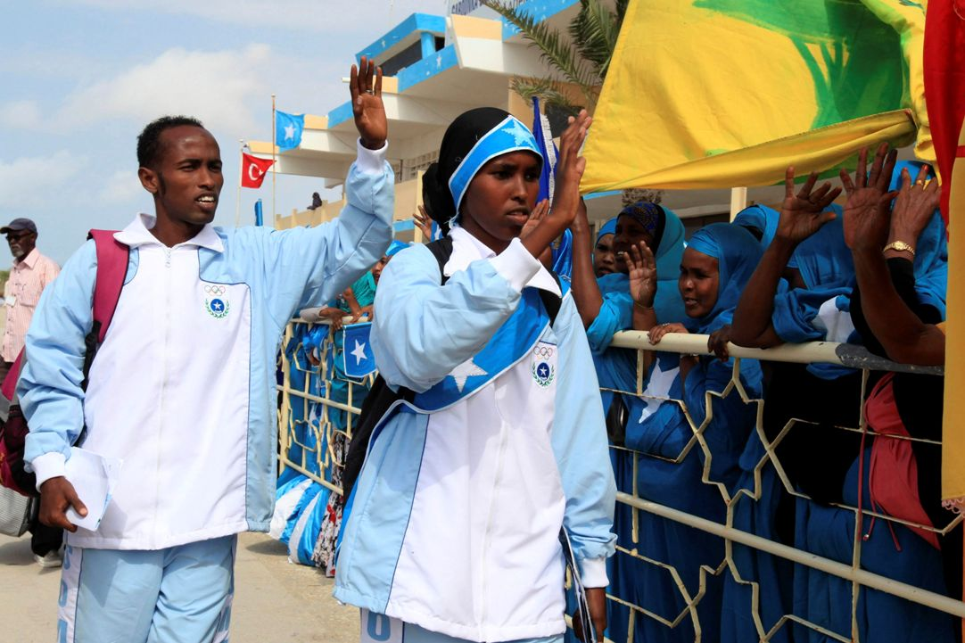 Mohamed Hassan (L) and Zamzam Farah, Somalia's representatives to the 2012 Olympics wave as they depart from the Aden Abdulle International Airport in Somalia's capital Mogadishu, July 17, 2012. Rarely able to travel to international meets, no Somali athlete qualified for the London Games outright. Each national Olympic committee is eligible for two guaranteed places -- one for a man, one for a woman -- in athletics. REUTERS/Feisal Omar (SOMALIA - Tags: SPORT ATHLETICS SOCIETY OLYMPICS)