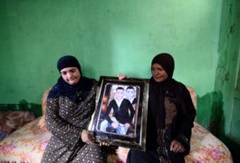 Meseda Abdel-Wahab (R), mother of teenager Fares Ezzat, and his aunt Halawethorn Abdel-Wahad pose holding a photograph of him at the family home in the village of Meit Massoud in Aga, Egypt, November 16, 2016. REUTERS/Stringer